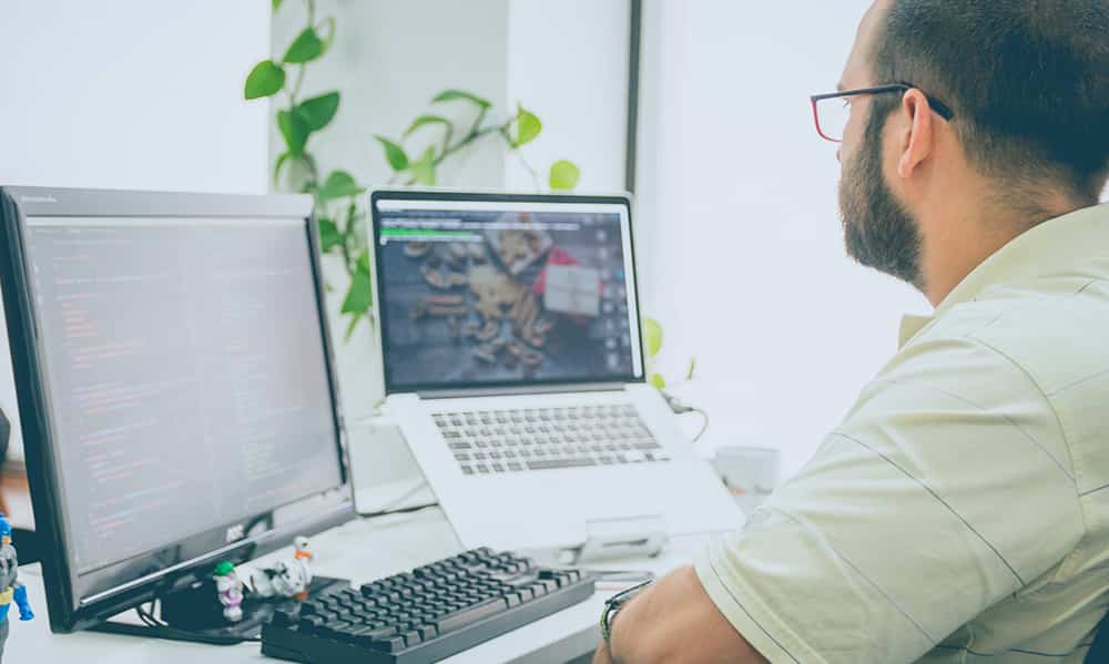 person working with two monitors