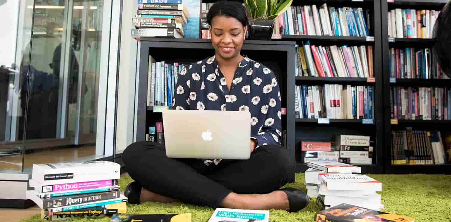 woman with her laptop surrounding by programming books