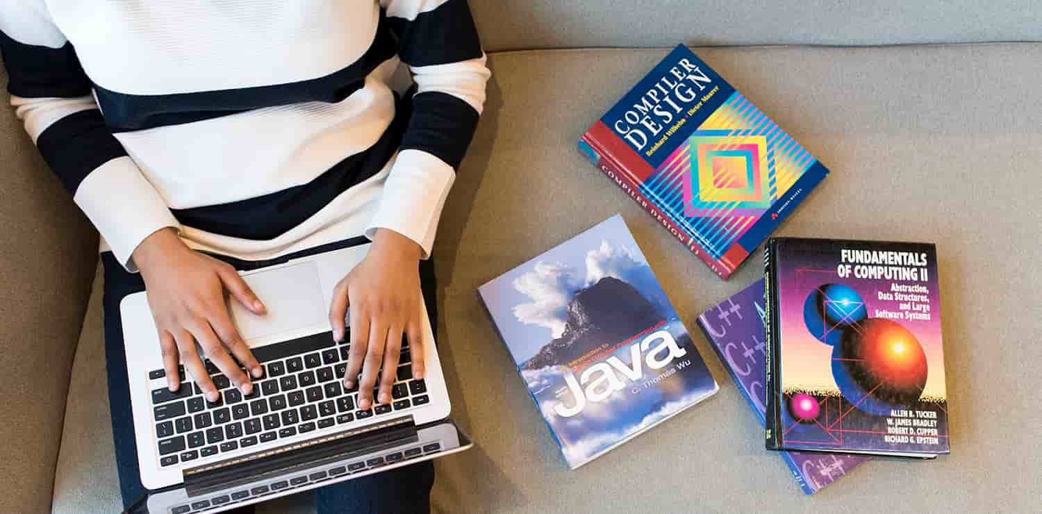 woman with her laptop sitting next to programming books