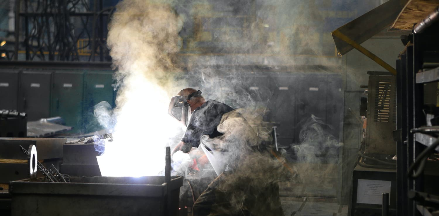 person welding with smoke coming off of work table