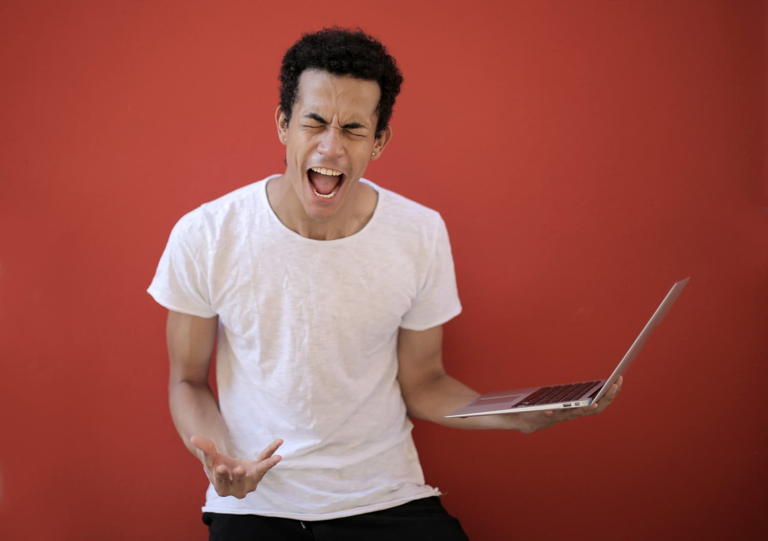 man screaming at laptop, frustrated with technology